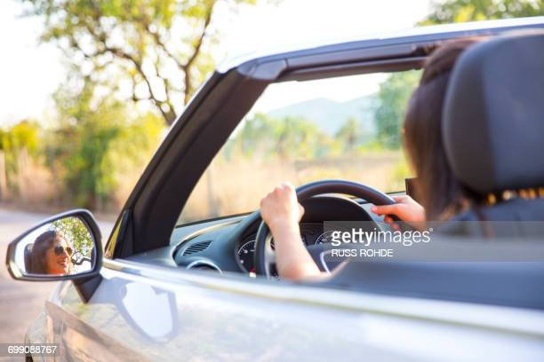 Wing mirror view of young woman driving on rural road in convertible, Majorca, Spain