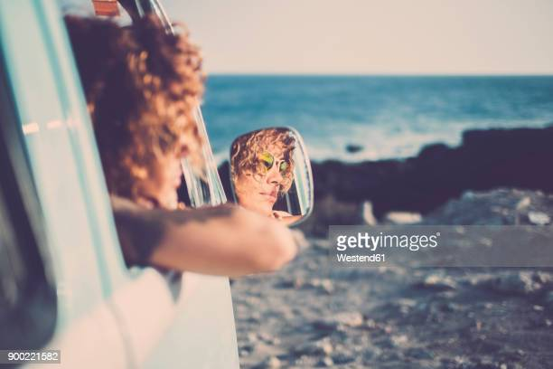 wing mirror with mirror image of woman looking out of a car - side view mirror stock photos and pictures