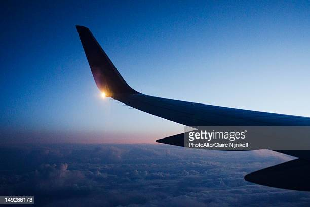 Wing of airplane in flight at dusk