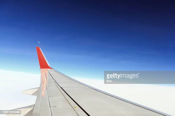 wing of an airplane above the clouds - vertical stabilizer stock pictures, royalty-free photos & images