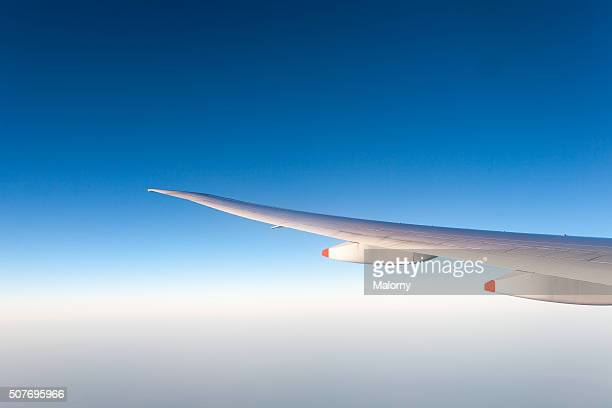 Wing of an airplane against clear blue sky. Boeing 777