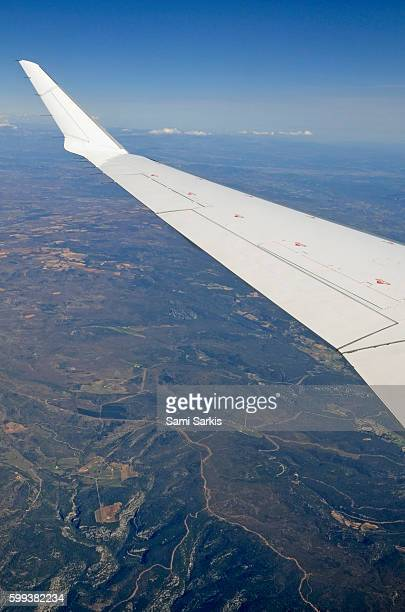 Wing of flying airplane over French Alps, France, Europe