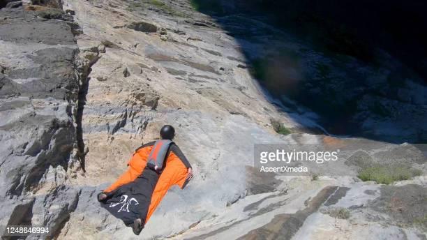 il volantino della tuta alare salta dalla cresta della montagna - solo un uomo di età media foto e immagini stock