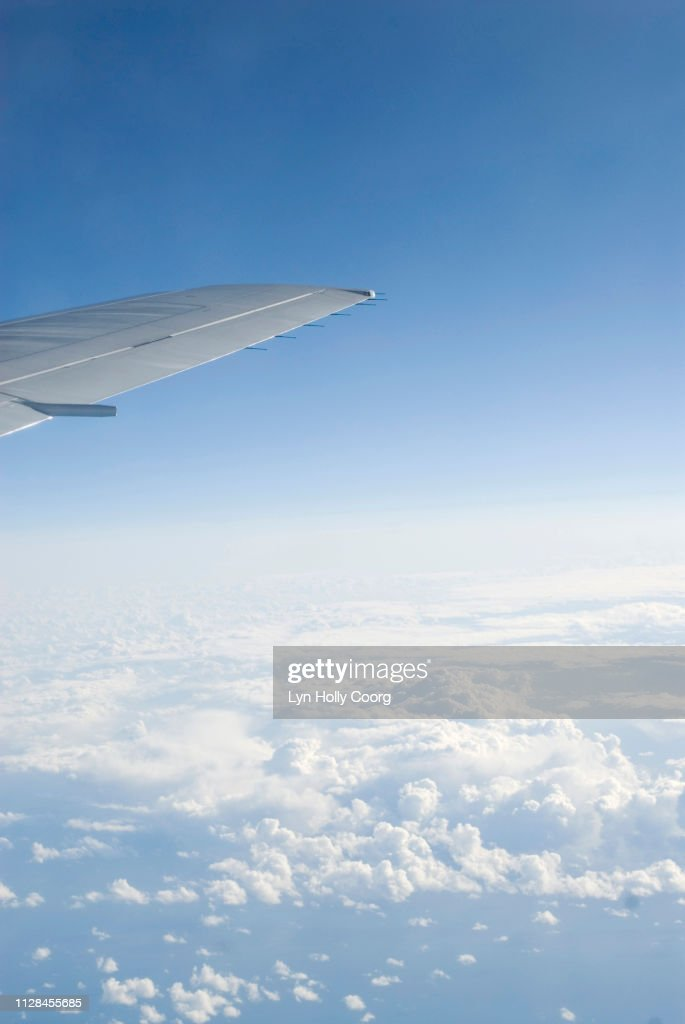 Wing tip of plane in cloudy blue sky : Stock Photo