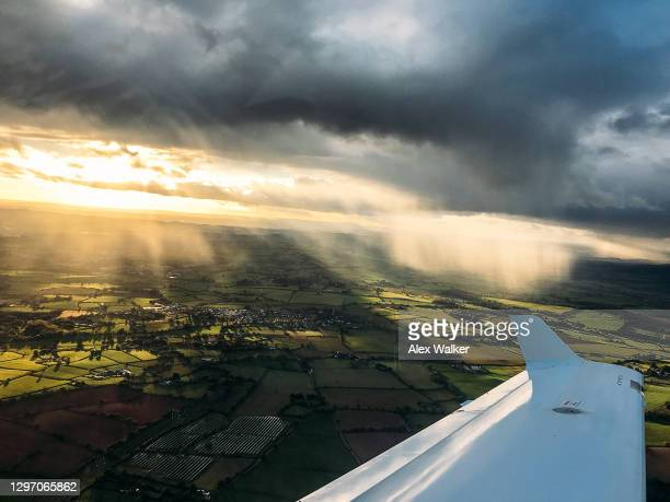 wing view from small private aircraft with heavy rain showers - horizon over land stock pictures, royalty-free photos & images
