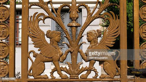 winged female figure of iron fence, athens, greece - geometrical architecture stock photos and pictures