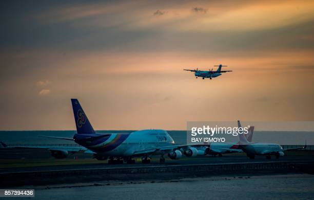 A Wings Air ATR 72 aircraft makes its final approach for landing as other aircraft wait along a taxiway for departure at the Ngurah Rai International...