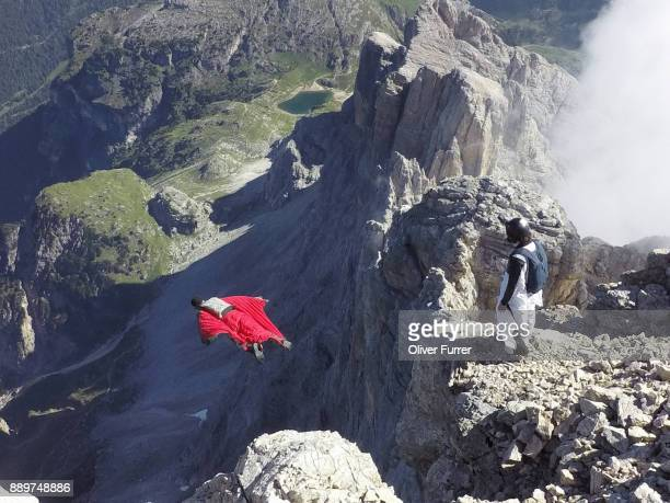 Wingsuit BASE jumper exited from a cliff and his friend is watching his proximity flight.