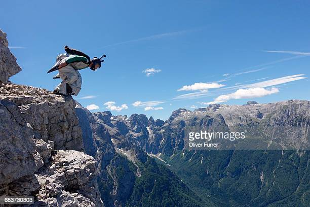 wingsuit base jumper getting ready to jump from cliff, italian alps, alleghe, belluno, italy - anticipation stock pictures, royalty-free photos & images