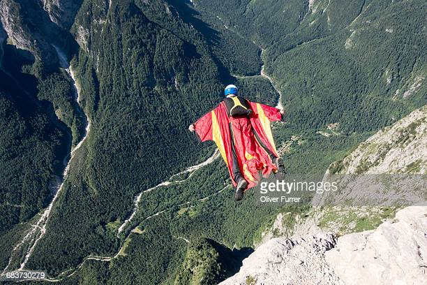 Wingsuit BASE jumper is flying down, Italian Alps, Alleghe, Belluno, Italy