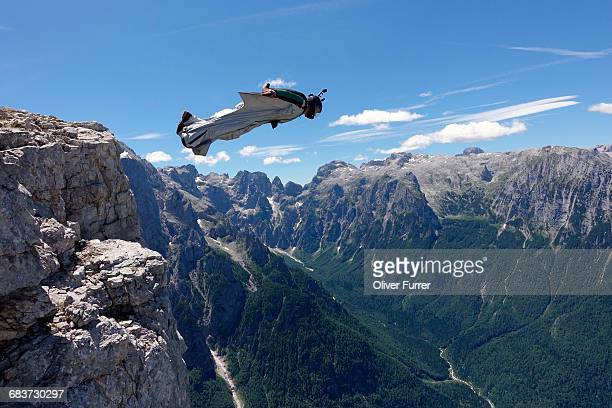 Wingsuit BASE jumper is flying from a cliff Italian Alps, Alleghe, Belluno, Italy