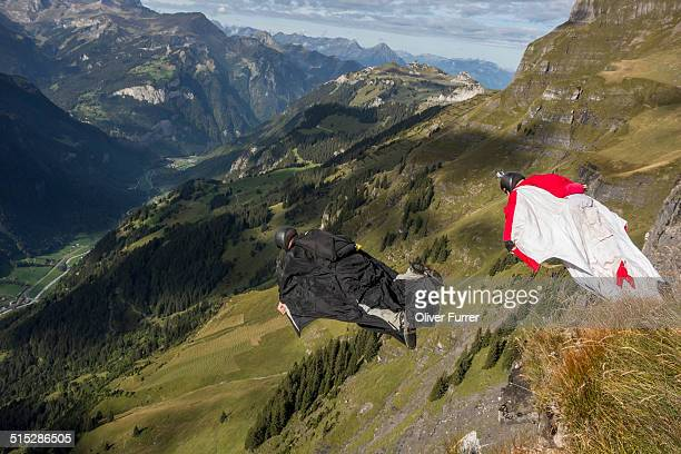 Wingsuit BASE jumpers are flying from a cliff down