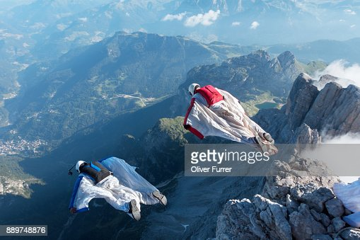 Wingsuit BASE jumpers exited from a cliff and are proximity flying together downwards into the valley.