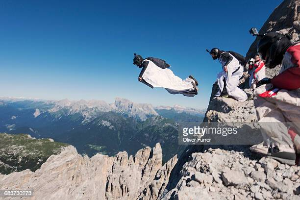 Wingsuit BASE jumping team jumping from cliff, Italian Alps, Alleghe, Belluno, Italy