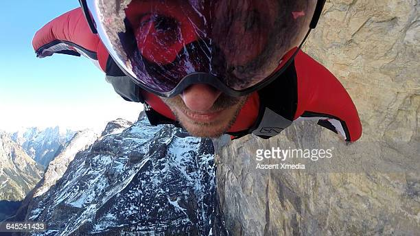 Wingsuit flier airborne over mountain face
