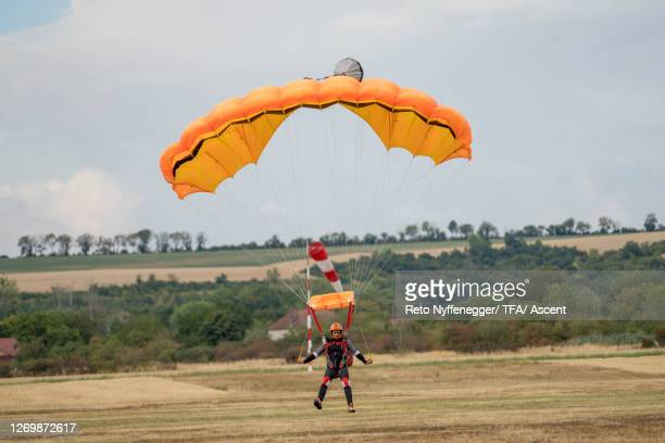 wingsuit flier comes in for landing, parachute open - landing touching down stock pictures, royalty-free photos & images