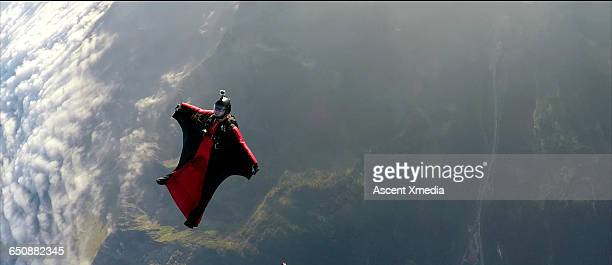 Wingsuit flier faces backwards in mid air flight