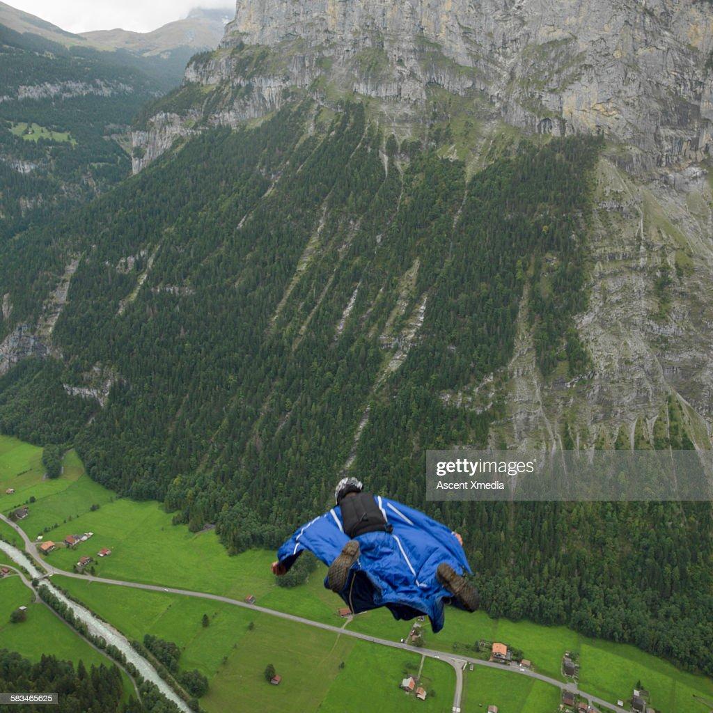 Wingsuit flier in airborne descent towards valley : Stock Photo