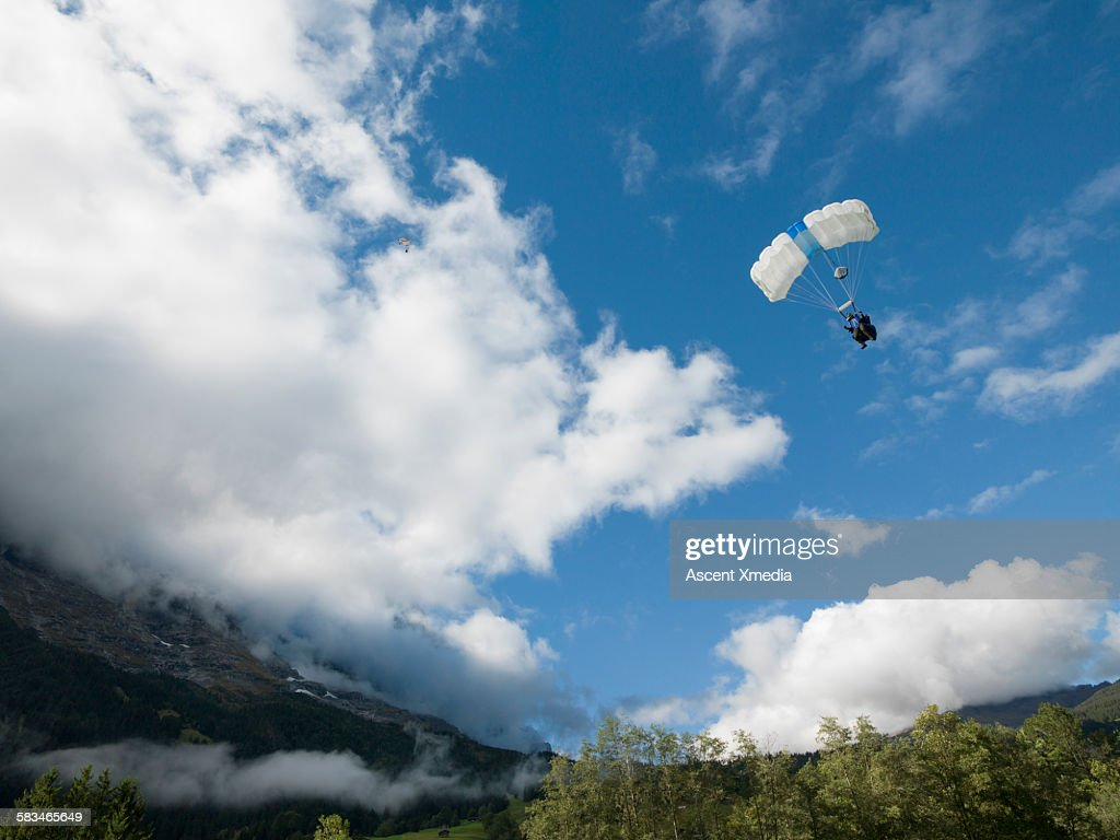 Wingsuit flier in final descent over mountains : Stock Photo
