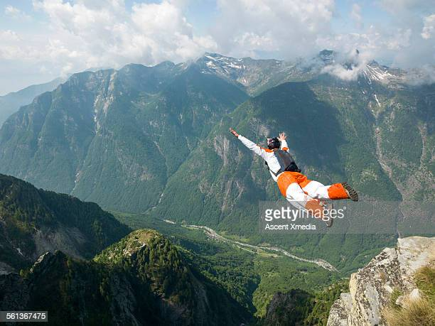 Wingsuit flier launches at cliff edge, into valley