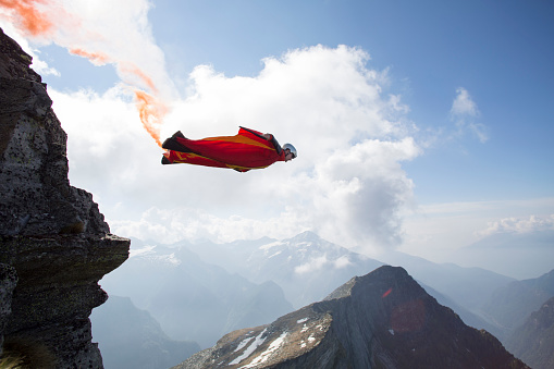 Wingsuit flier launches at cliff edge, smoke trail - gettyimageskorea
