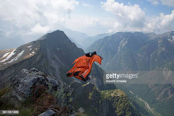 Wingsuit flier launches from cliff edge, valley