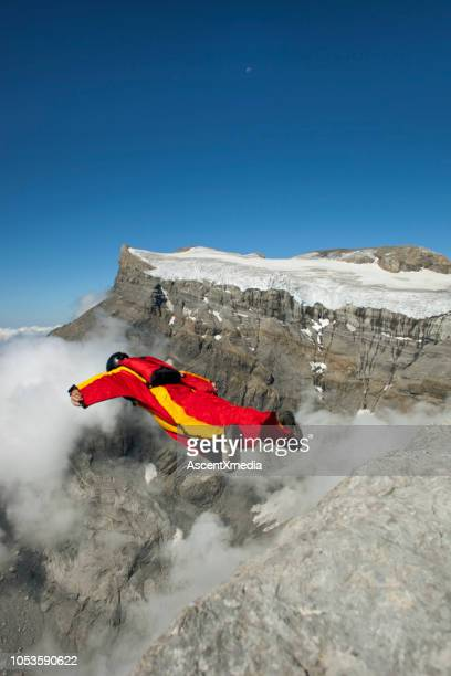 wingsuit flier launches from cliff, in mountains - ascent xmedia stock pictures, royalty-free photos & images