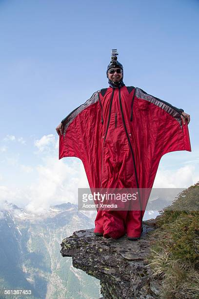 Wingsuit flier spreads wings at cliff edge