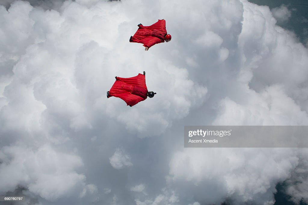 Wingsuit fliers glide above clouds, mountains