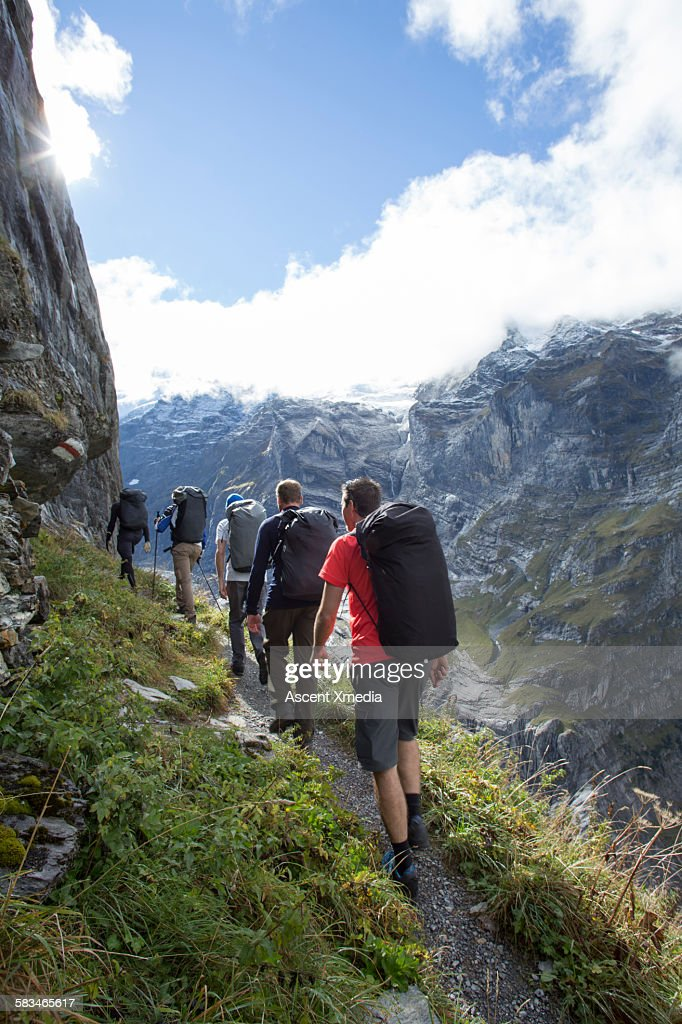 Wingsuit fliers hike up mountain trail, to launch : Stock Photo