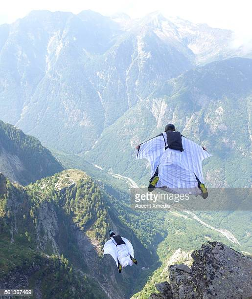 Wingsuit fliers launch at cliff edge, in tandem
