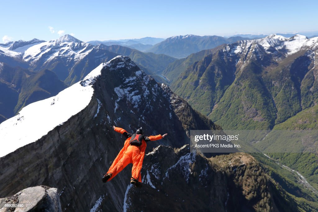 Wingsuit flyer airbourne above mountains : Stock Photo