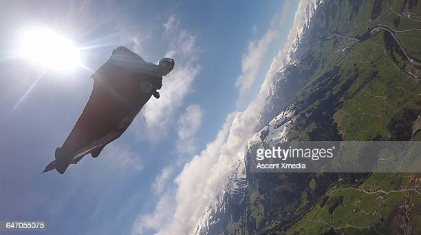 Wingsuit flyer in mid-air flight over mountains