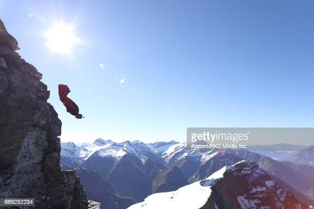 Wingsuit flyer jumps from cliff edge, mountains