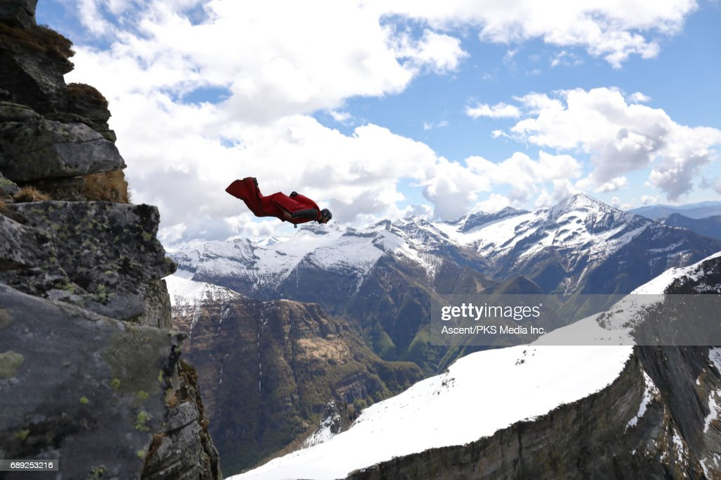 Wingsuit flyer jumps from cliff edge, mountains : Stock Photo