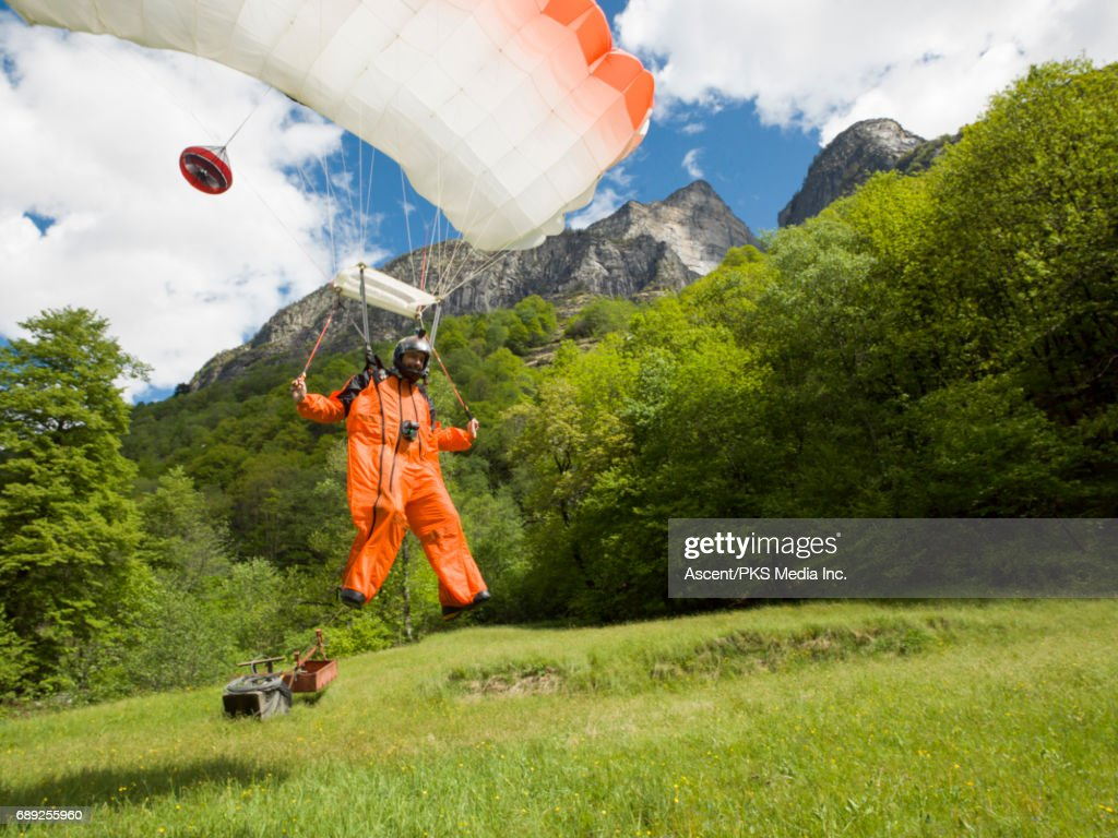 Wingsuit flyer lands in green meadow, mountains : Stock Photo