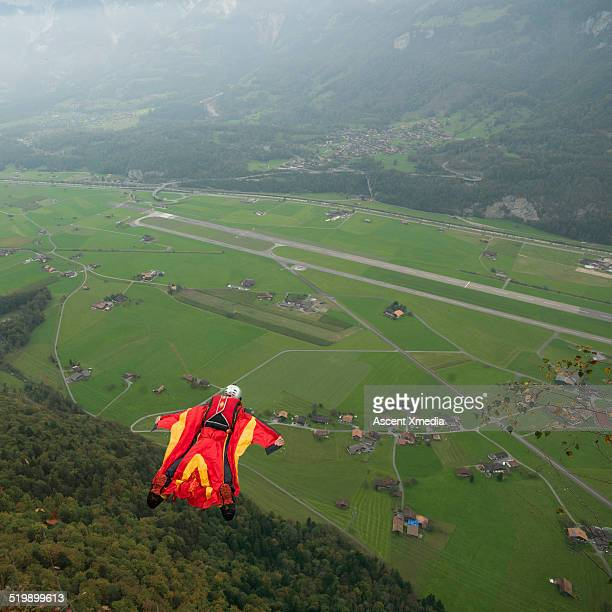 Wingsuit flyer, mid-air descent from cliff, valley