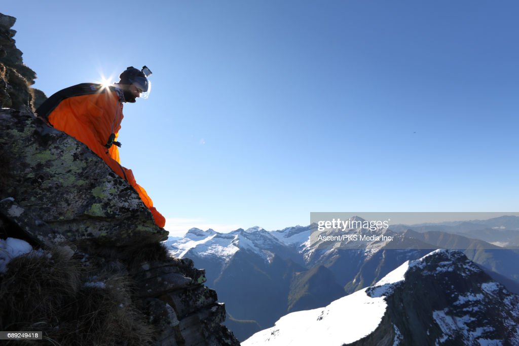 Wingsuit flyer prepares to jump from cliff edge, mountains : Stock Photo