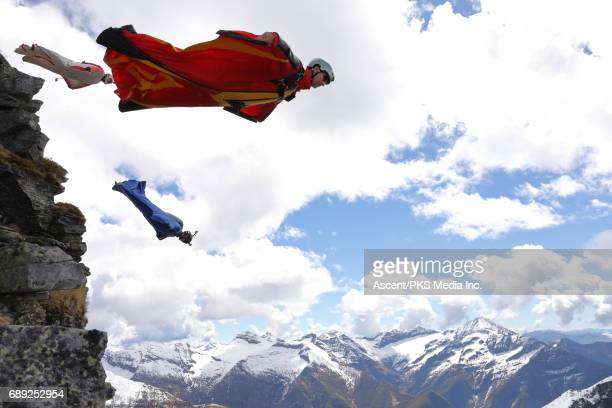 Wingsuit flyers jump from cliff edge, mountains