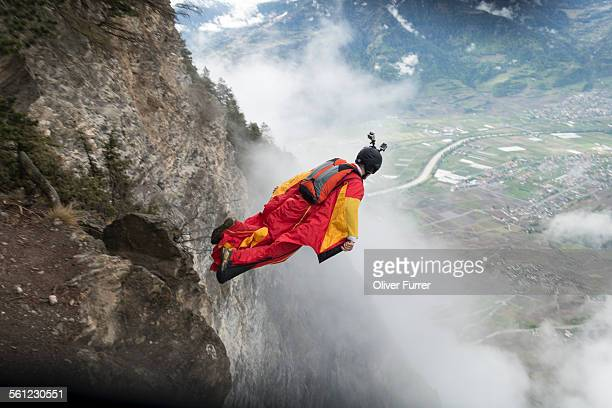 Wingsuit jumper exiting down from a cliff