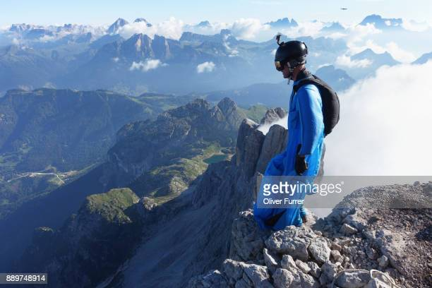 Wingsuit jumper is standing on the BASE exit and watching over the cliff edge. Full concentration before spreading the wings and lift off.