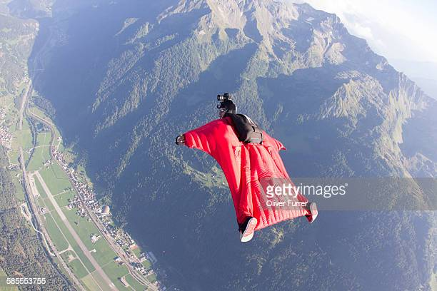 Wingsuit pilot flys over an airport in the sky