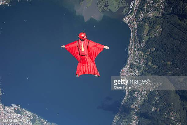 Wingsuit skydiver pilot flying over lake, Locarno, Tessin, Switzerland
