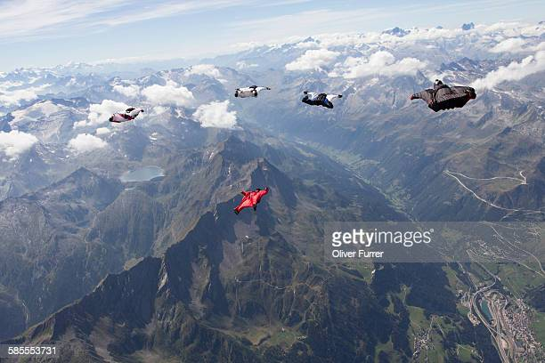 wingsuit skydivers are flying together in the sky - swiss alps stock pictures, royalty-free photos & images