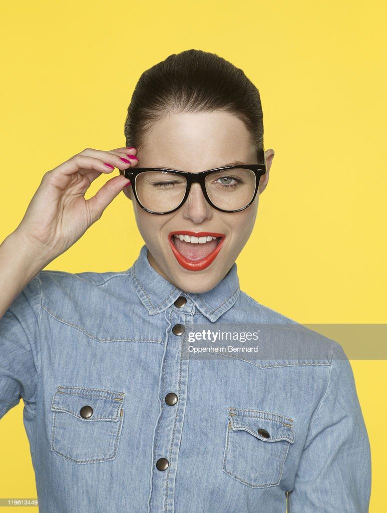 Winking woman in retro glasses and denim shirt