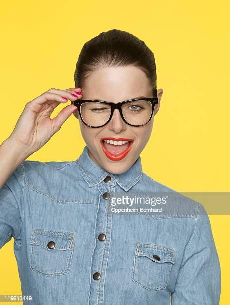 winking woman in retro glasses and denim shirt - fundo amarelo - fotografias e filmes do acervo