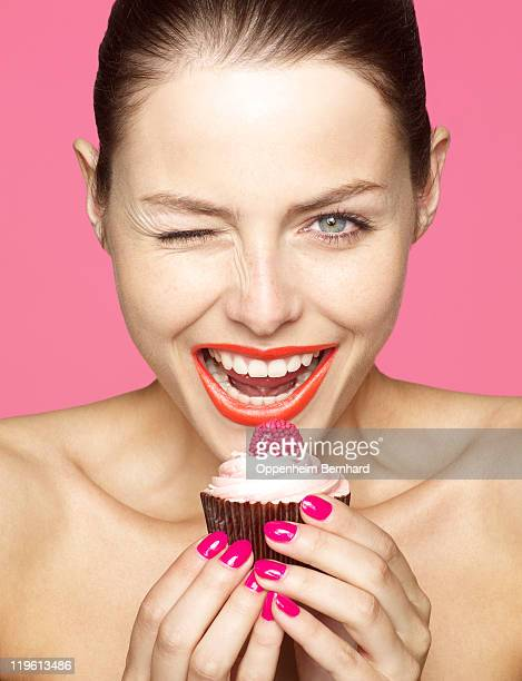 winking young female holding cupcake