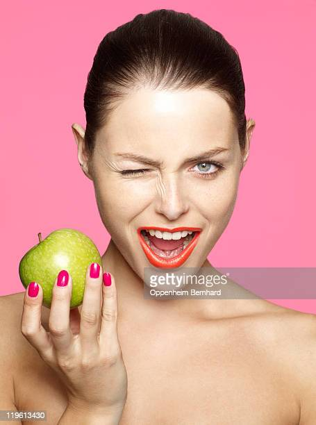 winking young female holding green apple