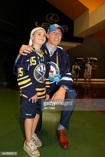 Winnepeg Jets Logan Stanley poses with a fan after being selected 18th overall during round one of the 2016 NHL Draft on June 24 2016 in Buffalo New...