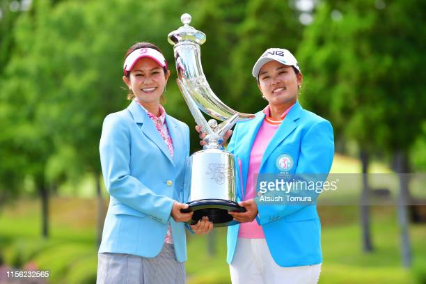 Winner Ai Suzuki of Japan receives the trophy from the tournament ambassador Ai Miyazato during the award ceremony following the final round of the...